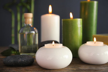 Spa composition with candles and cosmetic on table