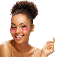 Smiling beautiful woman with pink patches on her face. Portrait of african american woman with perfect skin on white background. Skin care concept