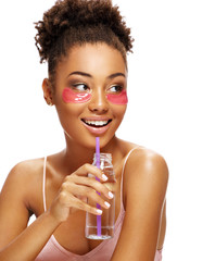 Beautiful girl with pink eye patches on her face and holds bottle of clean water. Photo of young african american girl isolated on white background. Youth and Beauty