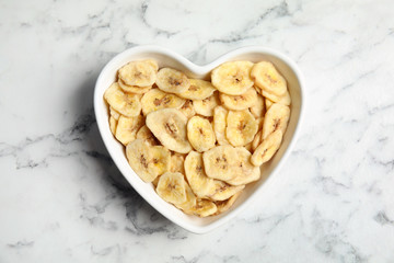 Heart shaped plate with banana slices on marble table, top view. Dried fruit as healthy snack
