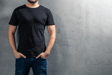 Young healthy man with black T-shirt on concrete background with copyspace for your text. Picture without model face.