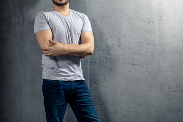 Young healthy man with grey T-shirt on concrete background with copyspace for your text. Picture without model face.