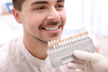 Dentist checking young man's teeth color, closeup