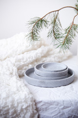 A rustic concrete plate on a white Christmas decorated table