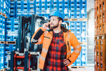 Worker in logistics warehouse on the phone receiving instructions