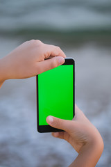 Young boy holding black smartphone in hands with blank empty green screen while standing at beach of hotel resort. Kid watching something at mobile cellphone with chroma key screen background.