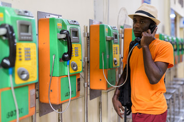 African tourist man talking on payphone and thinking