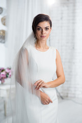 Portrait of gorgeous bride woman with beautiful make up in classic wedding dress in the bright studio