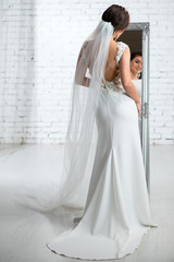 Back view of bride wearing gorgeous elegant wedding dress with long loop while standing near the mirror in the bright studio.