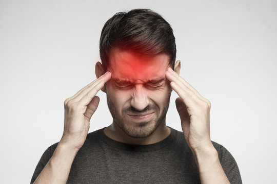 Portrait of young man isolated on gray background, suffering from severe headache, pressing fingers to temples with closed eyes