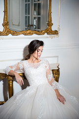 Elegant brunette bride in white wedding dress sitting near thevintage mirror in the hotel room with classic interior.
