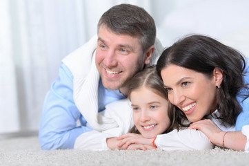 Happy parents and daughter lying on floor in room