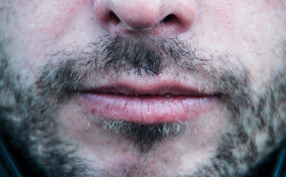 Beautiful thin men's lips and light unshaven face close up
