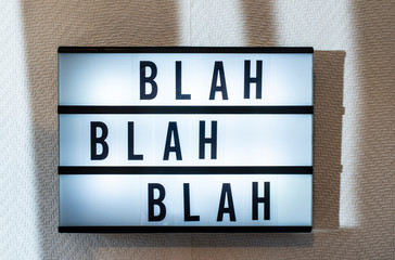 "Message ""blah blah blah"" on illuminated board. Boring concept with text. Black letters blah-blah on white wallpaper wall."