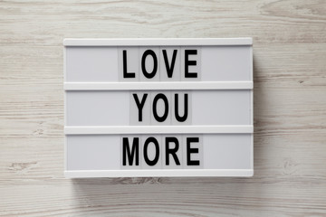 Modern board with text 'Love you more' on a white wooden background, top view. Valentine's Day 14 February.