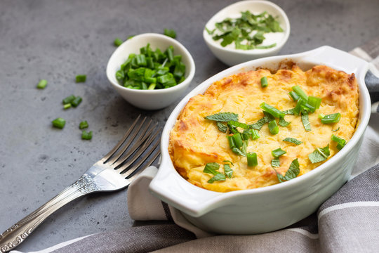 Potatoes casserole with cheese and green onion served with sour cream and mint. Vegetarian food. Copy space.