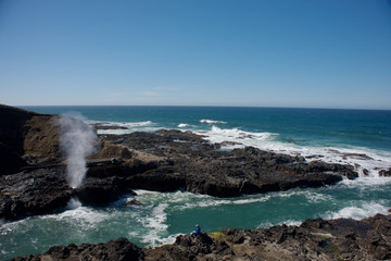 The Spouting Horn at Cape Perpetua on the Oregon Coast. A man watching the feature across a inlet of water.
