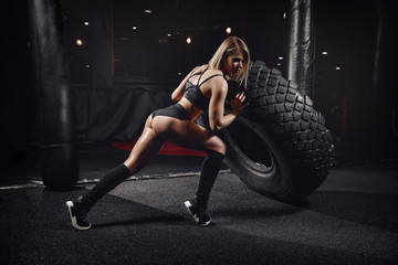 Beautiful woman tire wheel in gym. Workout fitness concept.