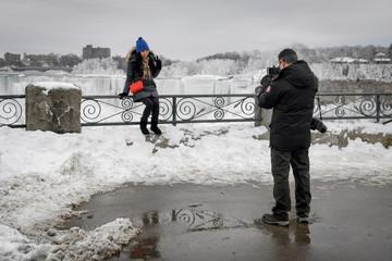 A couple takes a photo of ice formed around Niagara Falls due to subzero temperatures during a visit to Niagara Falls
