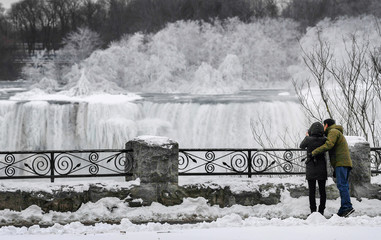 A couple takes a photo of ice ice formed around Niagara Falls due to subzero temperatures during a visit to Niagara Falls