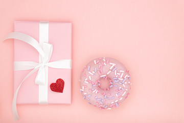 Valentine's Day, love concept. Mock up frame with gift box and white ribbon, heart symbol accessories, dessert violet donut on paper coral background. Flat lay, top view