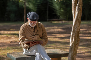 Old man sitting on the bench reading a book