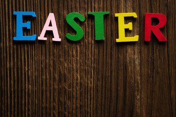 "the word ""Easter"" is laid out on a wooden background in colored letters"