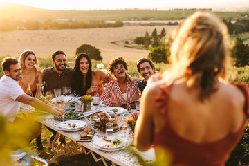 Woman taking picture of friends having dinner party