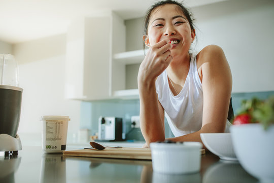 Healthy woman standing in the kitchen and smiling