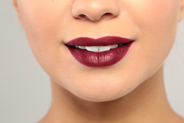 Young woman wearing dark lipstick on gray background, closeup