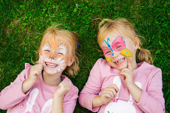 two little girls with colorful painted faces having fun on the grass