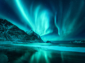 Spoed Fotobehang Nachtblauw Amazing aurora borealis. Northern lights in Lofoten islands, Norway. Starry sky with polar lights. Night winter landscape with aurora, sea with frosty coast and sky reflection, snowy mountains. Travel