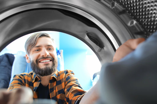 Man doing laundry in laundromat, view from the inside of washing machine