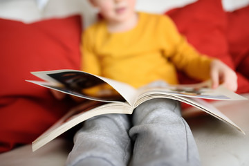 Little boy is sitting at home on the couch and reading a book. Learning to read.