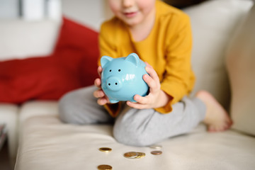 Little boy looks on moneybox and plans of what he can buy. Education of children in financial literacy. Money saving concept.