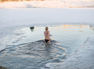 a woman dips into a hole in the lake