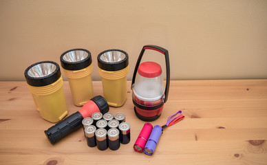 Flashlights and batteries laid out on a table prepared for a power outage.