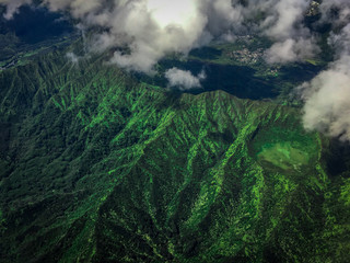 Vibrant, High Altitude Aerial Photo of a Mountain and Crater in Hawaii - Covered with Lush Green Trees and Vegetation on a Bright, Cloudy Day