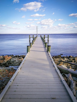 Colorful, Serene Photo of a Dock Extending Out To the Ocean - with a Patch of Rocks and Logs, and Calm Waters on a Bright, Mildly Cloudy Day in the Mid Atlantic United States
