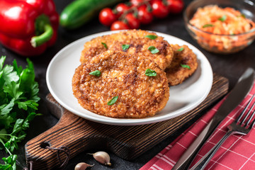 Cutlets lie on a white plate. Chicken cutlets lie among the vegetables on a black stone table.