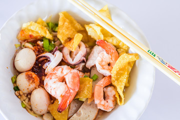 "Seafood noodle Tom Yum in white bowl on white background, Thai food, Street food..Egg noodles served ""dry"" with seafood."