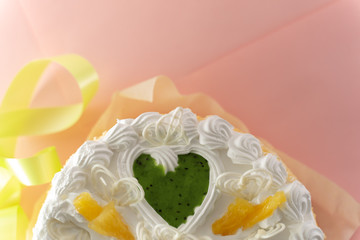 white cake on a colored background with ribbons shot from above