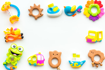 Handmade toys for newborn babies, plastic and wooden rattle on white background top view copy space frame