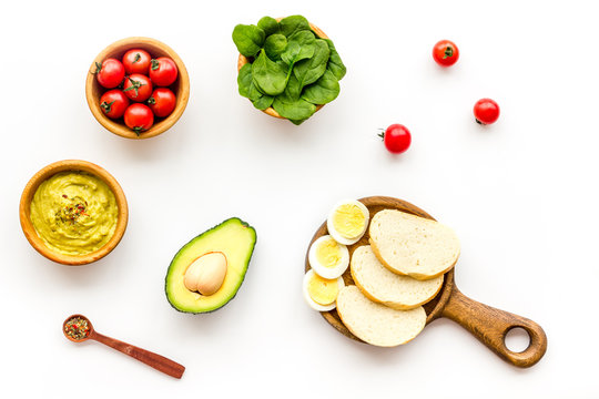 Healthy breakfast. Toasts with vegetables and guacamole on white background top view