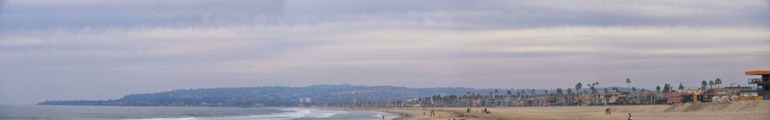 View from Mission Beach in San Diego, of Piers, Jetty and sand, around surfers, including warning signs, palm trees, waves, rocks, boats and horizon views. Pacific Ocean. California, United States.