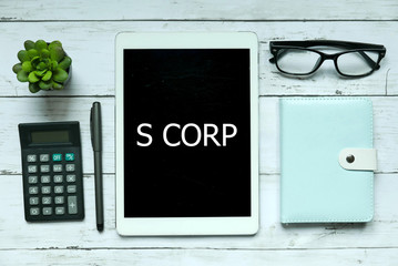 Business concept. Top view of plant,calculator,glasses,pen,notebook and tablet written with S Corp on white wooden background.