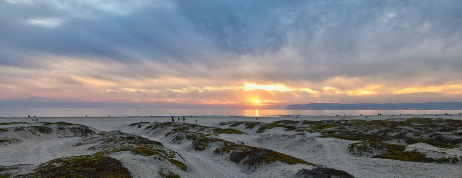 Coronado Beach in San Diego by the Historic Hotel del Coronado, at sunset with unique beach sand dunes, panorama view of the Pacific Ocean, silhouettes of people walking and boats in California, Unite