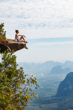 Young girl traveler  sitting on a cliff