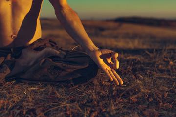 Yogi man meditating at sunset on the hills. Lifestyle relaxation emotional concept spirituality harmony with nature