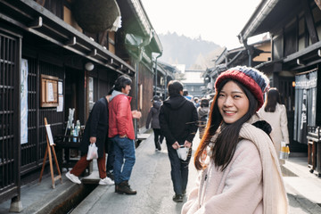 Happy Asian Girl with pink overcoat in Takayama old town, Gifu, Japan during cold weather in winter.
